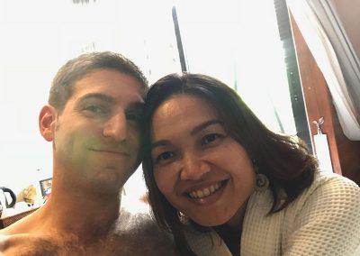 honeymoon couple travelers smiling selfie by the window in Butterfly Pea hotel room