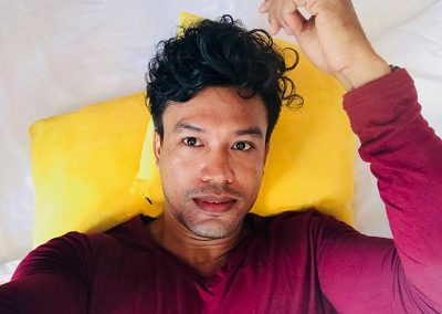 solo traveler wearing a purple sweater taking a selfie laying on the Butterfly Pea hotel room bed with yellow pillows